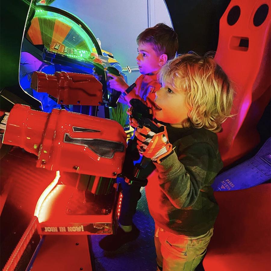 Kids playing arcade machines
